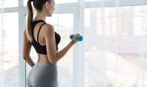 Unrecognizable fitness woman exercising with dumbbells, copy space